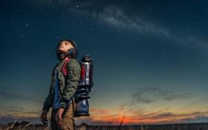 bambino con zaino che guarda il cielo al tramonto